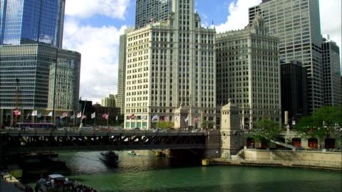 a ferry passes under the michigan avenue bridge in chicago. - ミシガン橋点の映像素材/bロール