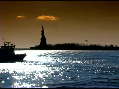 vídeos de stock e filmes b-roll de ferry passing statue of liberty in new york - figura feminina
