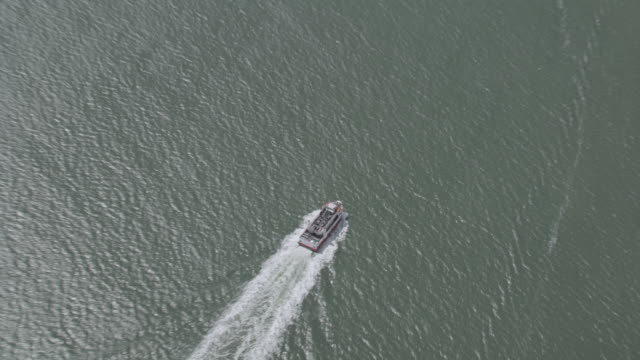 AERIAL Ferry traveling across the bay leaving a large wake behind it / San Francisco, California, United States