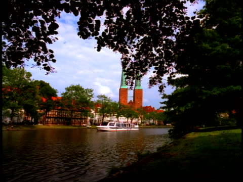 a ferry traverses a waterway near a cathedral and the waterfront village of lubeck, germany. - lübeck stock-videos und b-roll-filmmaterial