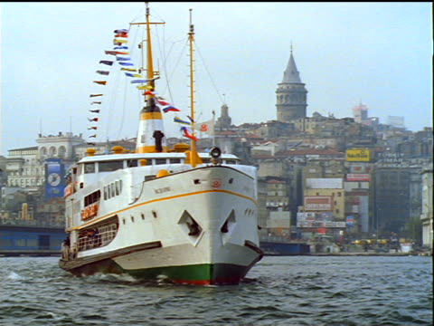 ferry turning on bosporus with istanbul skyline in background / turkey - ausflugsboot stock-videos und b-roll-filmmaterial