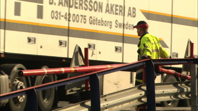 A ferry worker closes the gate after a truck boards the ferry in Gothenburg, Sweden..