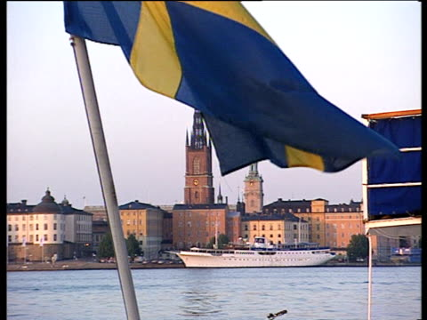 ferryboat moored in stockholm harbour with church spire in centre. swedish flag on pole flaps in front of camera calm sea in foreground - swedish flag stock videos and b-roll footage