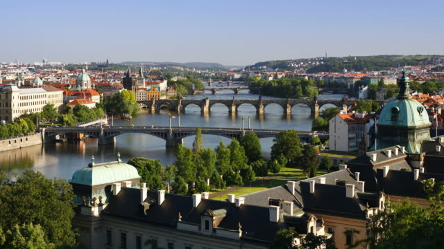 ferryboats navigate through bridge arches on the vltava river in downtown prague. - フラッチャニ城点の映像素材/bロール