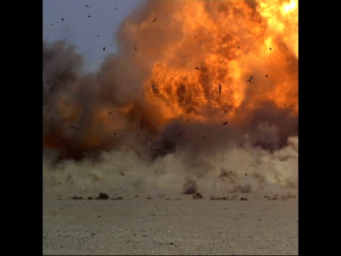 vidéos et rushes de fertiliser bomb explosion; slow motion / time lapse wide shot of van and other truck in desert as fertiliser bomb exploding and shrapnel flying... - fade out