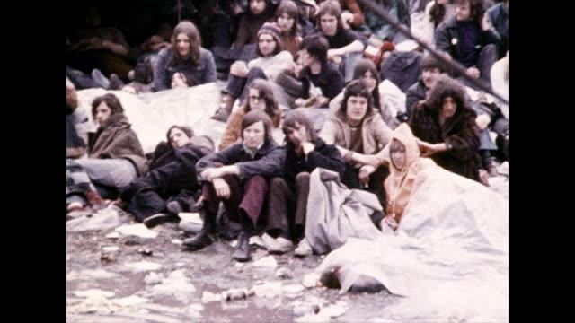 festival goers cope with rain; 1972 - レインコート点の映像素材/bロール
