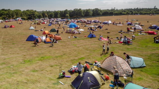 festival goers setting up camp at music festival, uk. - camping stock videos & royalty-free footage