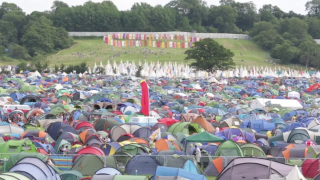 Festival goers walk around the tents in the camping fields at the Glastonbury Festival at Worthy Farm Pilton on June 25 2015 in Glastonbury England