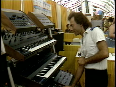 festival technology exposition tent, man demonstrates keyboard, electronic music equipment as crowd watches. - piano key stock videos & royalty-free footage