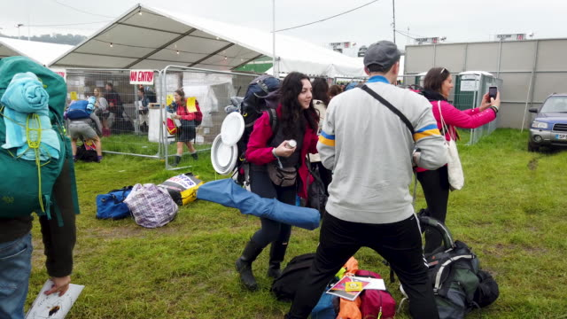 vidéos et rushes de festival-goers carry their belongings and tents to the camping areas as the gates are opened during day one of glastonbury festival at worthy farm,... - audience de festival