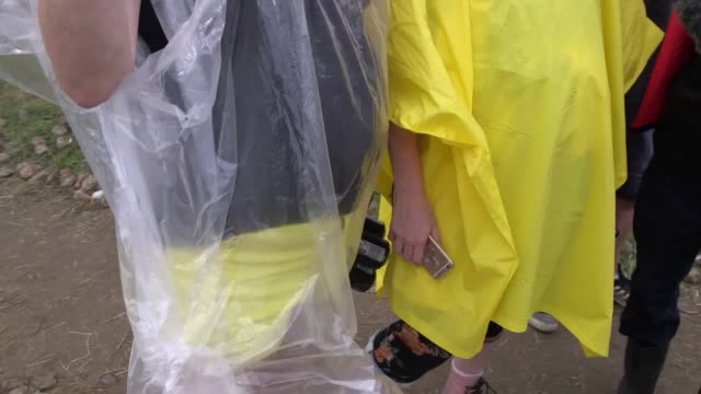 festival-goers enjoy themselves despite a rainy start to the weekend at the isle of wight festival. - festival goer stock videos & royalty-free footage