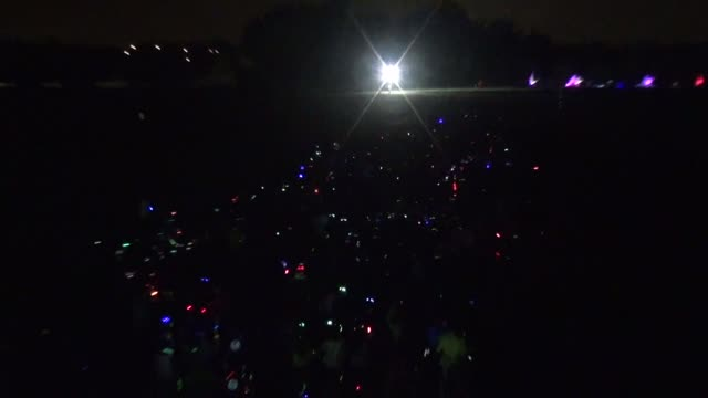 festive crowd awaits start of electric run nighttime - salmini 個影片檔及 b 捲影像