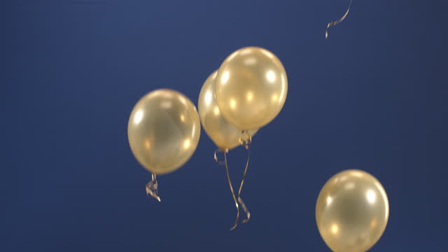 festive decoration - balloons - appear in the video as a gift for the holidays: valentine's day, birthday, christmas, a festive event or new year on a blue background. - birthday stock videos & royalty-free footage