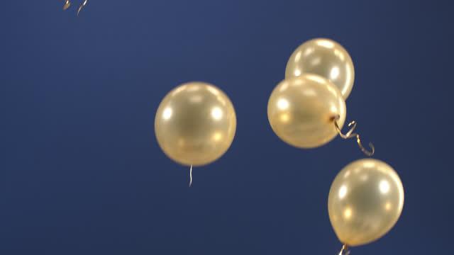 vídeos y material grabado en eventos de stock de decoración festiva - globos - volar en el vídeo como una sorpresa para las fiestas: día de san valentín, cumpleaños, navidad, un evento de gala o año nuevo sobre un fondo azul. - globo de helio