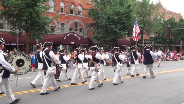 vidéos et rushes de festive fife and drum corps march down main street in saratoga springs ny leading the fourth of july parade - salmini