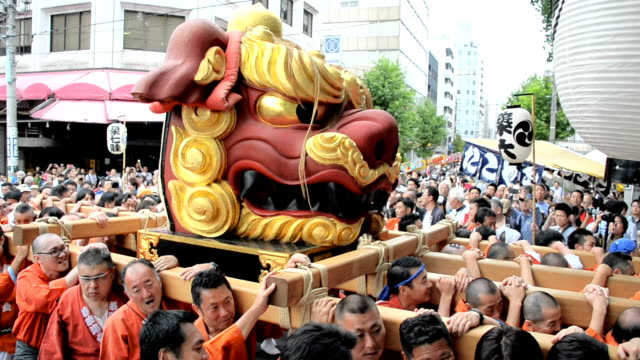 "festive parishioners of namiyoke inarijinja shrine in tokyo's chuo ward took turns bearing a 1.8-meter tall ""shishi"" lion with black teeth on a... - 籠点の映像素材/bロール"
