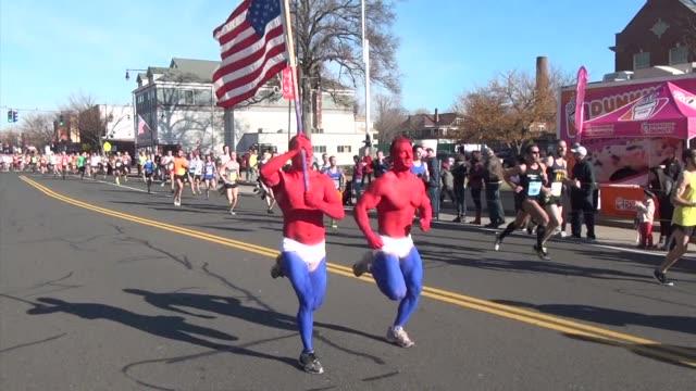 vidéos et rushes de festive running race, runners carry american flag - salmini
