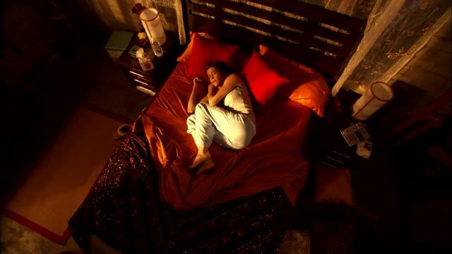 a feverish woman shifts uncomfortably on her bed. - 身体症状点の映像素材/bロール