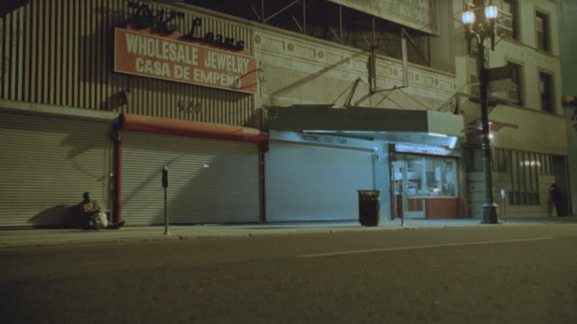 a few cars pass shops closed for the night in downtown los angeles. - persiana caratteristica architettonica video stock e b–roll