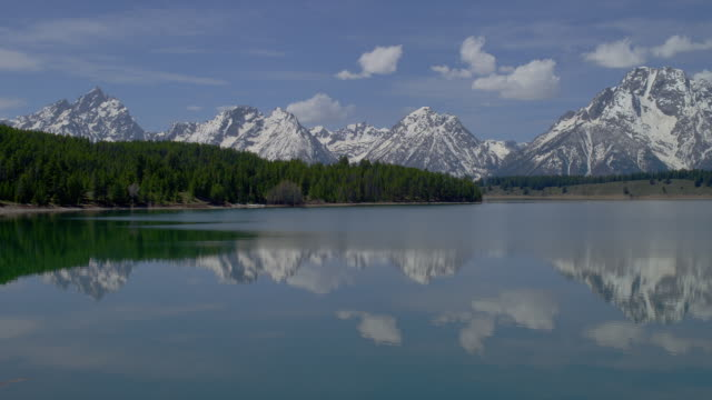 wide pan few clouds in blue sky above mt moran and teton range with snake river in foreground, grand teton national park, wyoming - mt moran stock videos & royalty-free footage