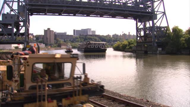 A few industrial railway cars travel on a train track near a river.