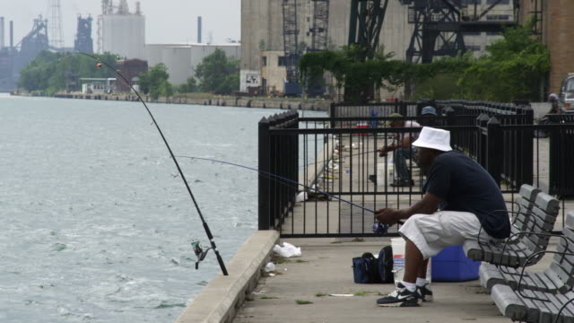 a few men fishing off the wharf in detroit. - fishing rod stock videos & royalty-free footage