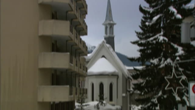 A few pedestrians walk along a snowy street past a church in Davos, Switzerland.