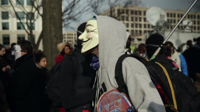 few protesters who wear v for vendetta masks are told to leave as they attempt to join the post-march rally on capitol hill. december 13 washington,... - アノニマス点の映像素材/bロール