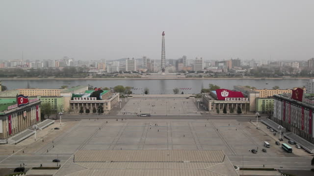 A few vehicles pass Kim II Sung Square.