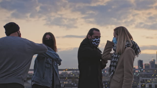 ffriends meeting during pandemic of coronavirus. elbow bumps. rooftop sunset - prevenzione delle malattie video stock e b–roll