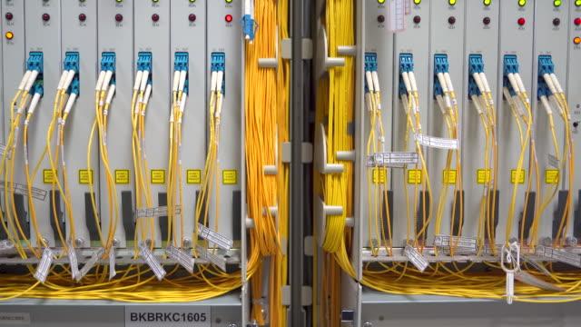 vidéos et rushes de câble de fibre optique relié à la boîte d'enceinte dans une salle de centre de données de technologie pour la communication à grande vitesse - fibre optique