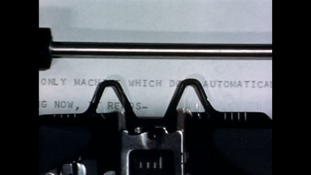 CU officer pulling ticker tape of code out of translation machine / feeds into a typewriter style machine / machine begins to type out text / CU of...