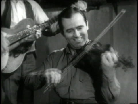 stockvideo's en b-roll-footage met 1946 montage fiddler and banjo player smile as they provide the soundtrack for square dancers - 1946