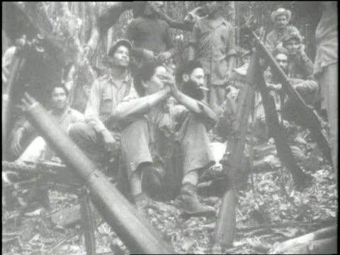 vidéos et rushes de fidel castro and his guerrilla soldiers sit around a campfire and eat roasted meat - révolution cubaine
