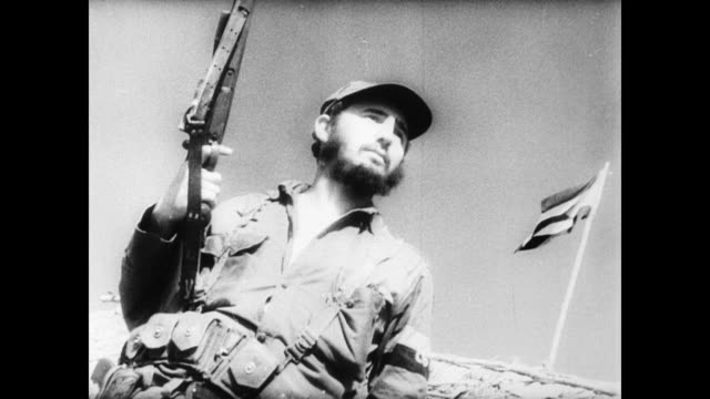 vídeos de stock e filmes b-roll de / fidel castro gives troops directions in the mountains / troops walk through the cuban jungle / troops fire on cuban military police / castro posing... - 1958