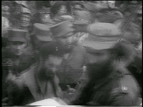 Fidel Castro in uniform walking toward camera in crowd / postrevolution Havana / newsreel