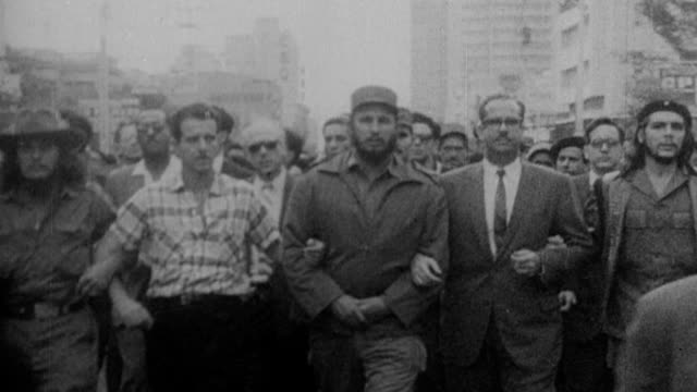 Fidel Castro marching in solidarity with civilians as announcer explains his seizure of American property in Cuba / worker chisels Cuba Telephone...