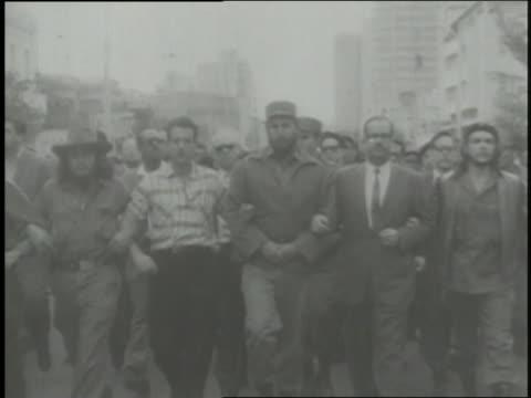 vidéos et rushes de fidel castro parades through the streets as a worker chisels a name off a building. - communisme