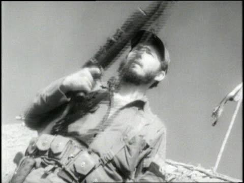 vidéos et rushes de fidel castro stands with a rifle in his hands - révolution cubaine
