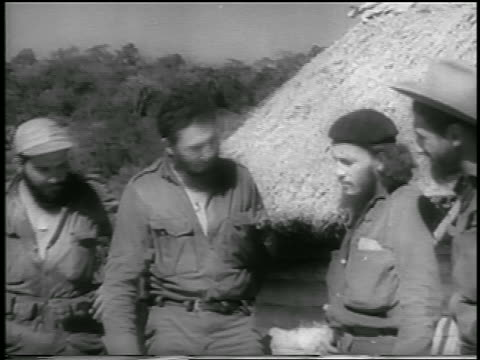 Fidel Castro talking to other guerrilla soldiers outdoors / Cuba / newsreel