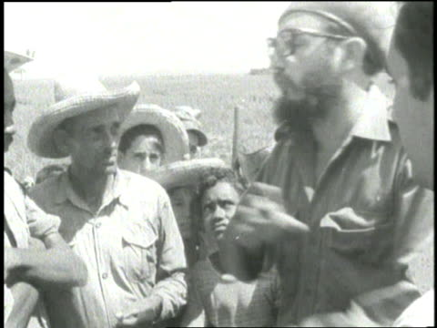 Fidel Castro talks with villagers while smoking a cigar