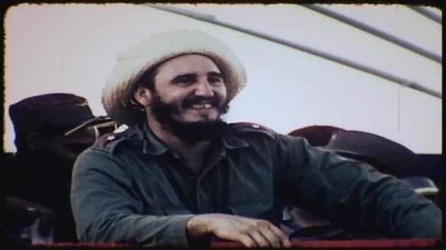 fidel castro wearing a staw hat looks out from stage speaks with others while waiting for events to begin - strohhut stock-videos und b-roll-filmmaterial
