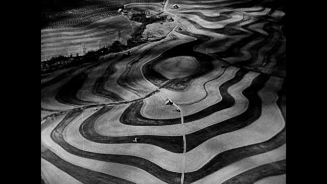 vídeos de stock e filmes b-roll de field after field of farmland / scenes of new boundaries and crop rotation / riveted soil fields in contrasting colors / suited farmers debate new... - 1942