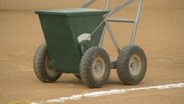 field chalker dry line marker chalk cart lines at a little league baseball game. - slow motion - チョークの跡点の映像素材/bロール
