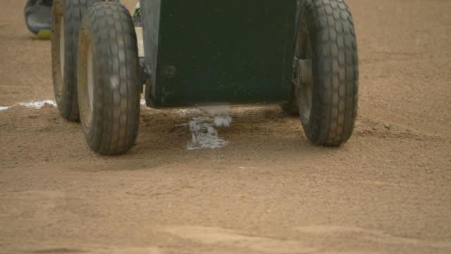 field chalker dry line marker chalk cart lines at a little league baseball game. - slow motion - チョーク点の映像素材/bロール