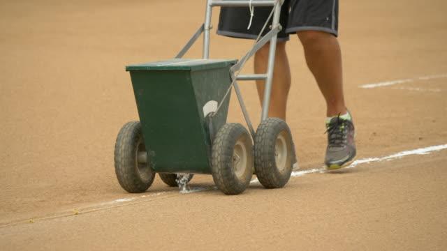 vídeos y material grabado en eventos de stock de field chalker dry line marker chalk cart lines at a little league baseball game. - slow motion - magnesio