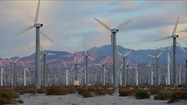 field of wind turbines turning with red mountain in distance. - abundance stock videos & royalty-free footage
