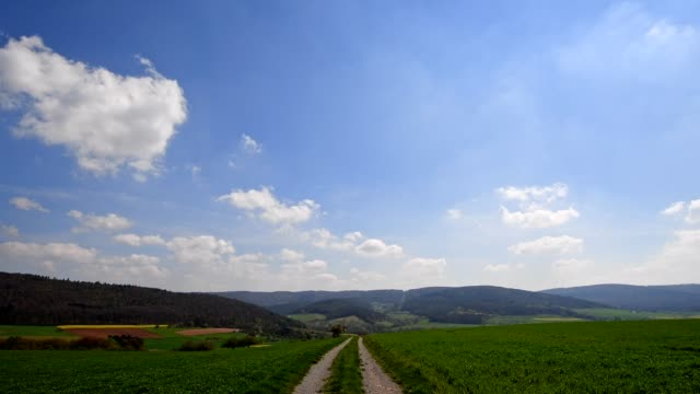 Field path with sun in countryside in spring, Eichelsbach, Bavaria, Germany