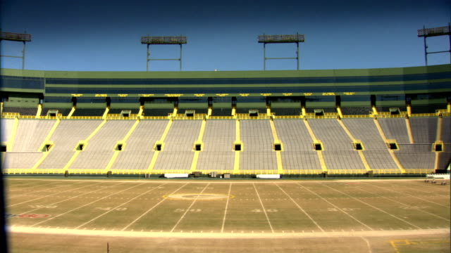 WS Field seats of empty stadium suites lights BG blue sky DOLLY BACKWARD REVEALS handrails of entrance ramp FG Packers football NFL sports