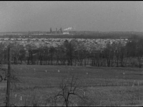 field w/ fencing markers houses behind tree line industrial buildings in distance possibly power station or sewer plant suburbs suburban lifestyle... - levittown pennsylvania stock videos and b-roll footage